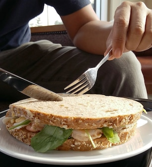 ナイフ、フォーク、サンドイッチ食べる人