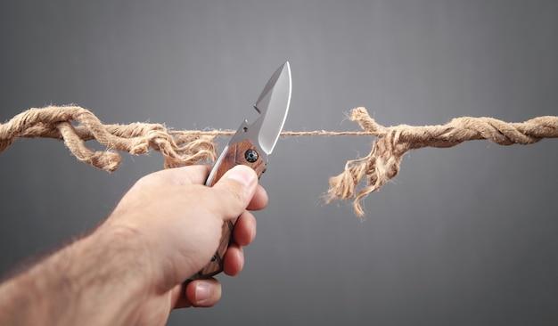 擦り切れたロープを切るナイフを持つ男。危険