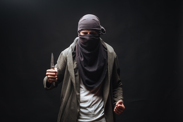 Man with knife and mask on dark background