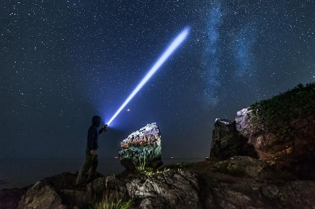 Человек с фонарем под звездным небом и млечным путем