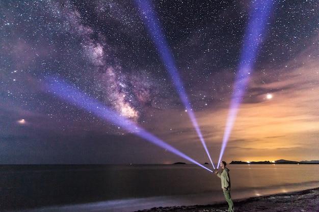 星空と天の川の下でランタンを持つ男