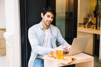 Man with laptop computer relaxing in cafe