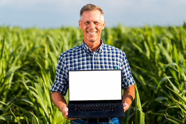Man with a laptop in a cornfield mock-up