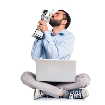 Man with laptop holding a trophy