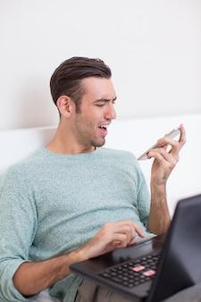 Человек с ноутбуком, сердито глядя на смартфон