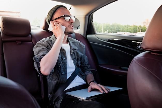 タクシーで仕事をする旅行で車の後部座席に電話をかけるラップトップを持つ男。