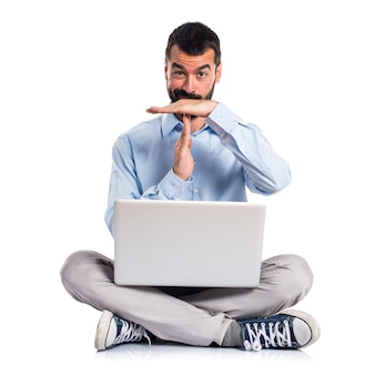 Man with laptop making time out gesture