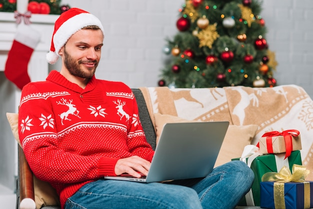 Man with laptop near present boxes