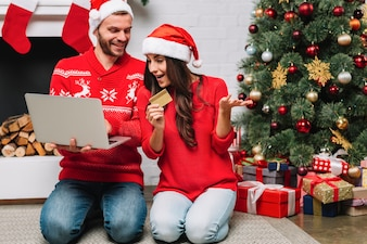 Man with laptop near woman with credit card