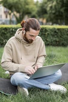 都市公園における屋外のラップトップを持つ男