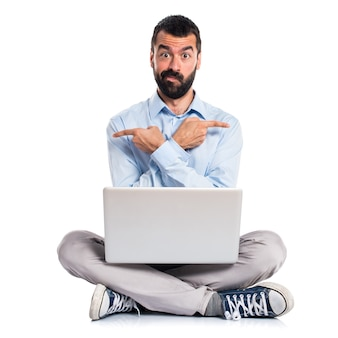 Man with laptop pointing to the laterals having doubts