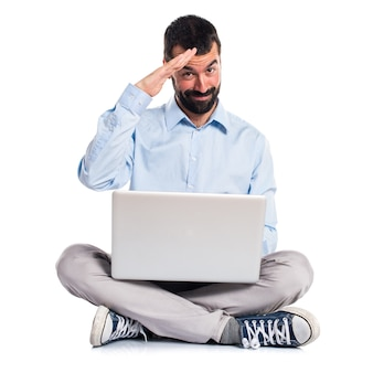 Man with laptop saluting