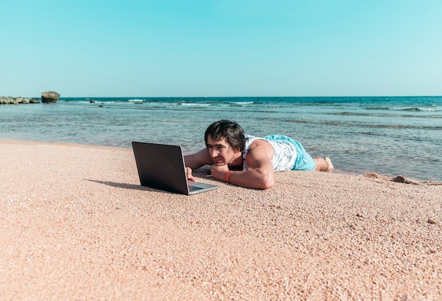 A man with a laptop on a sand is resting and working as a freelancer