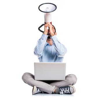 Человек с ноутбуком, кричащим на мегафон
