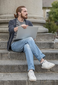 Man with laptop in steps