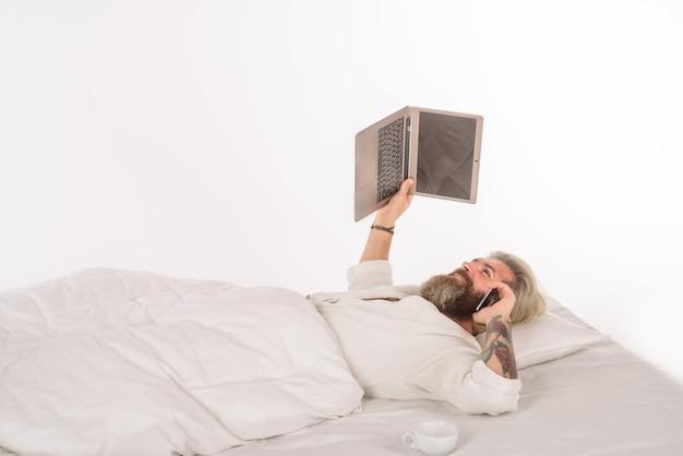 침대에서 일하는 노트북을 가진 남자 노트북과 스마트 폰을 가진 집에서 일하는 남자