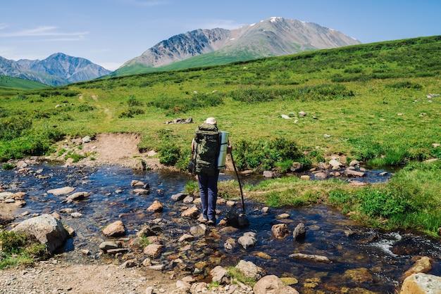 大きなバックパックを持つ男は、石の上に山の小川を横切る