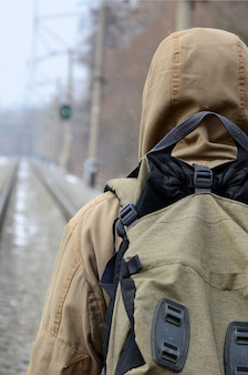 A man with a large backpack goes ahead on the railway track