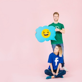 Man with laughing emoji speech bubble standing behind thoughtful woman