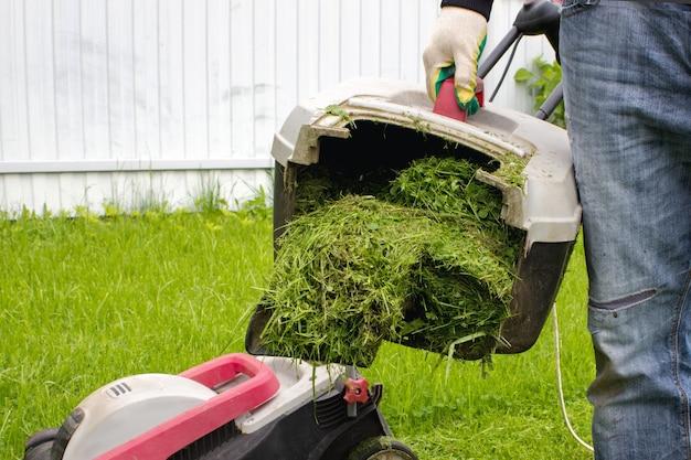 잔디 깎는 기계 잔디 수집기를 손에 가진 남자입니다. 잔디 깎는 남자. 원예 및 조경 개념입니다.