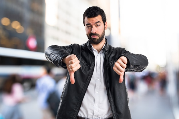 Man with leather jacket doing bad signal