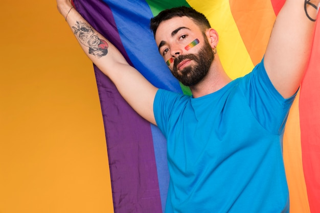 Man with lgbt rainbow on face with multicolored flag