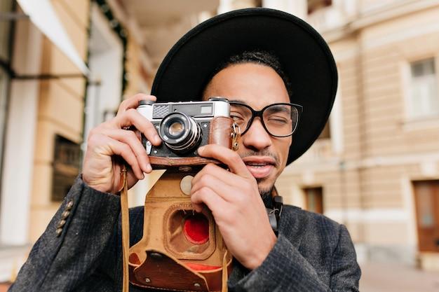 카메라로 사진을 찍는 밝은 갈색 피부를 가진 남자. 흑인 남성 사진 작가의 야외 클로즈업 초상화는 추운 날에 모자를 착용합니다.