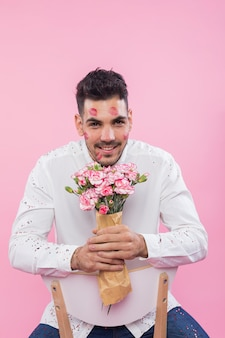 Man with lipstick kiss marks on face sitting with flowers