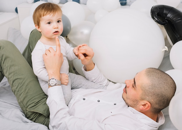 Man with little baby playing on bed near balloons