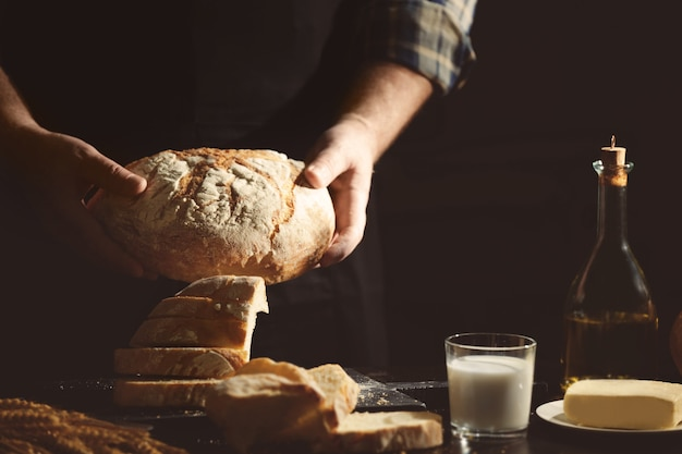 Man with loaf of bread in kitchen