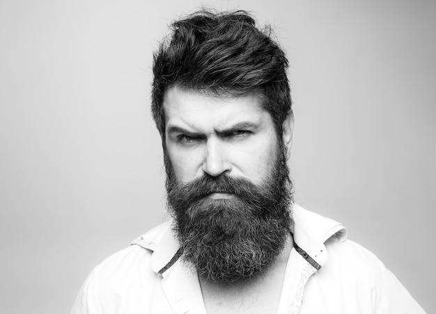 긴 수염, 콧수염 및 세련된 머리카락을 가진 남자. 엄격한 얼굴. 현대적인 헤어 스타일을 가진 남자가 미용사를 방문했습니다. 이발소 또는 미용사 개념.