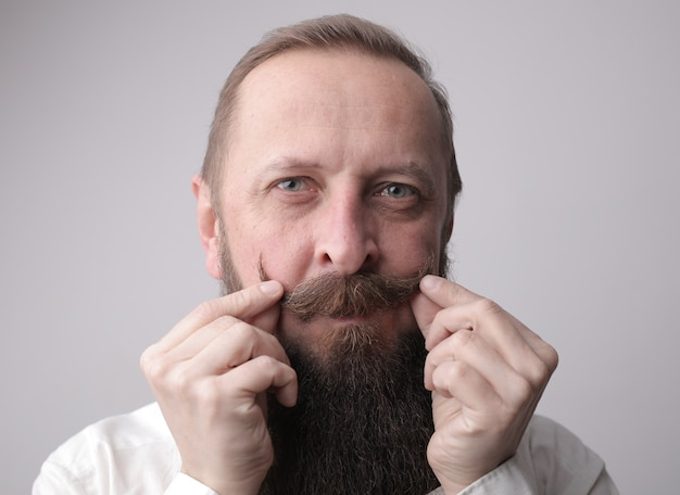 Uomo con una lunga barba e un paio di baffi che sorride mentre si trova davanti a un muro grigio