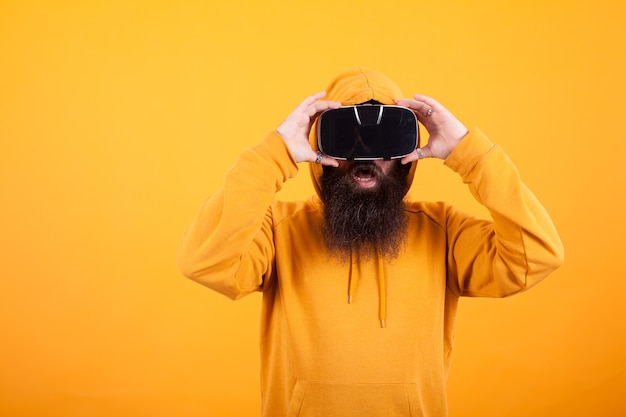 Человек с длинной бородой в гарнитуре виртуальной реальности выглядит потрясенным на желтом фоне. желтая толстовка с капюшоном. современные технологии. красавчик.