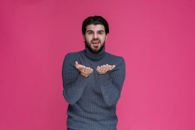 Мужчина с длинными волосами и бородой раскрывает руки и выглядит смущенным или неопытным.