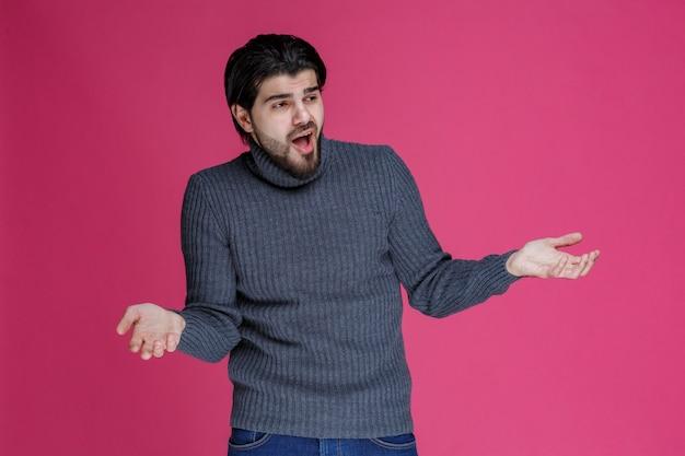 長い髪とあごひげを生やした男性は手を開き、混乱しているか、経験が浅いように見えます。