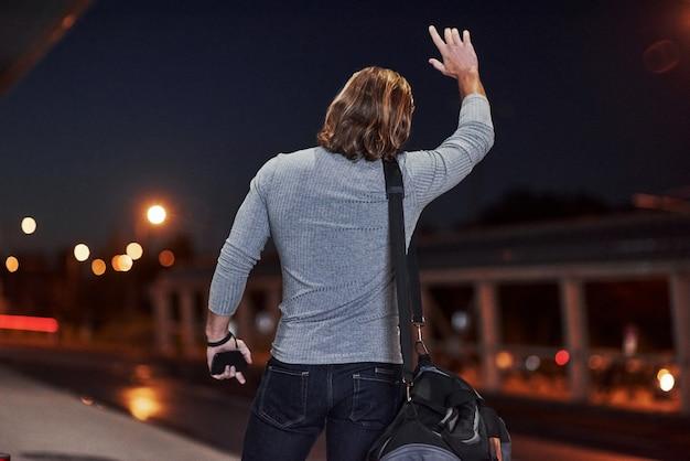 Человек с длинными волосами и дорожным багажом ждет такси, чтобы забрать его