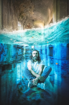 Man with long hair and beard meditates underwater