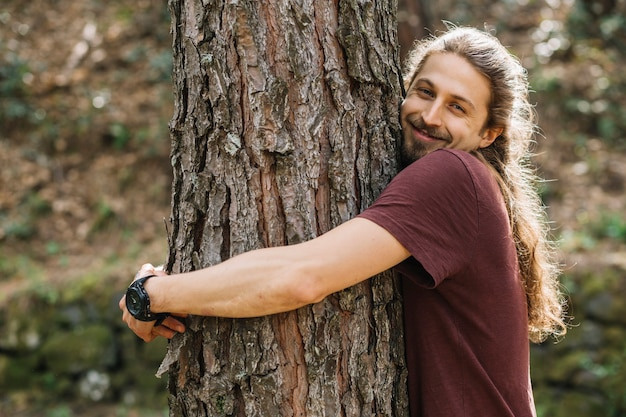 Man with long hair hugging a tree