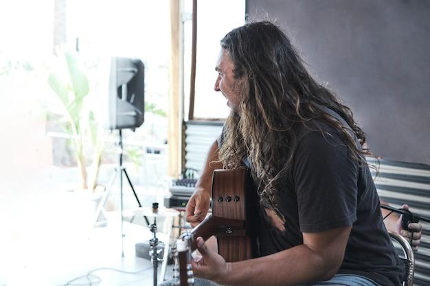 ライブショーでギターを弾く長い髪の男