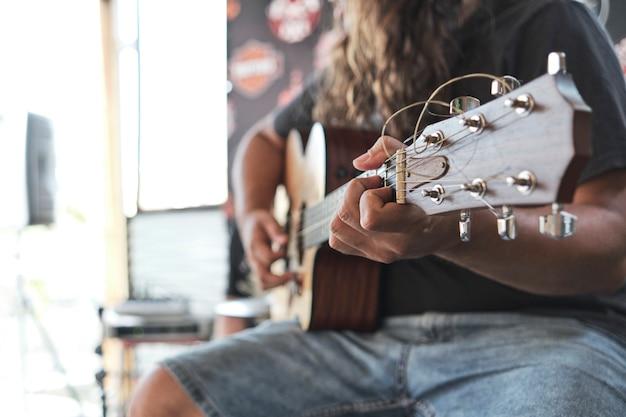 ショーでギターを弾く長い髪の男