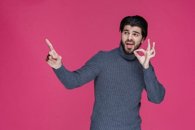 Человек с длинными волосами и бородой, делая знак нулевого круга в руке.