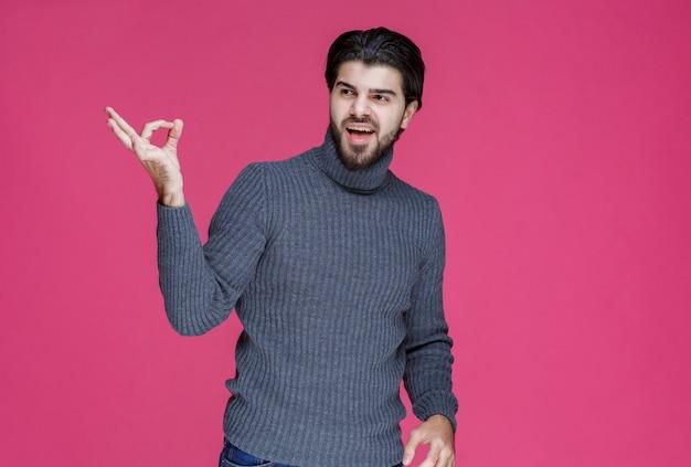 Uomo con i capelli lunghi e la barba che fa il segno del cerchio zero in mano.