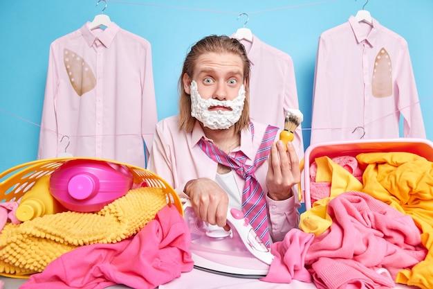 Uomo con lunghi capelli rossi impegnato a stirare i vestiti e a radersi allo stesso tempo essendo di fretta mentre dormiva