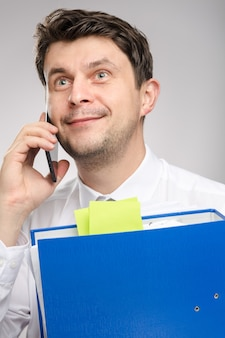 Man with lot of documents worker of the month speaking by phone with client