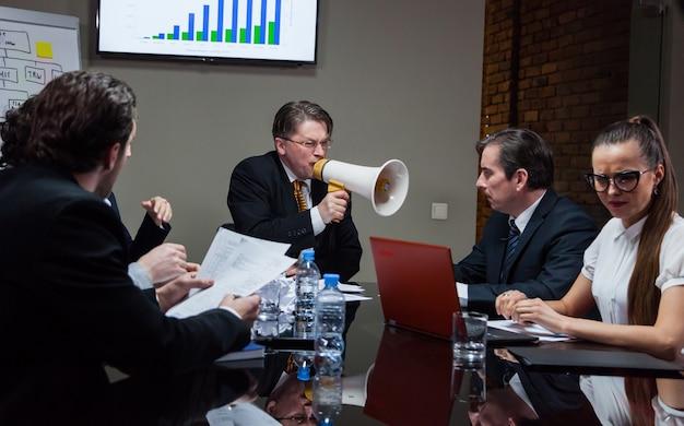 会議中にテーブルで従業員に向かって叫んでいるスピーカーを持つ男。