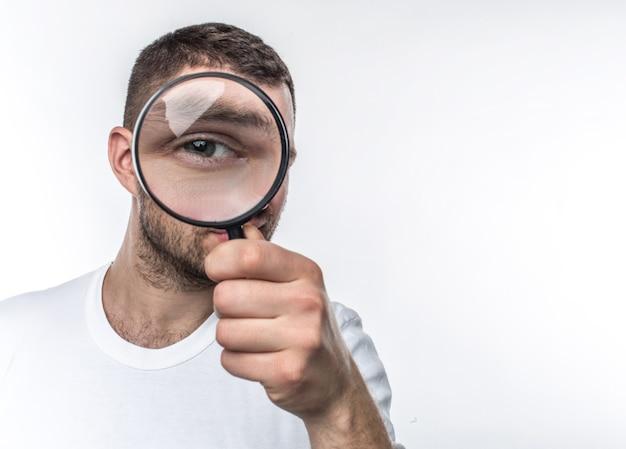 확대경을 가진 남자가 정면을 바라보고 유리를 통해 눈을 보이고 있습니다. 그는 탐정입니다. 흰색 배경에 고립