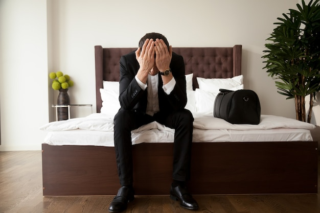 Man with luggage grieves at hotel after divorce