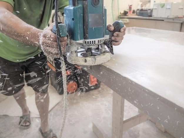 カウンタートップのアクリル石の機械加工を持つ男。