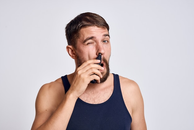 A man with a machine for removing hair from a nose in a black t-shirt