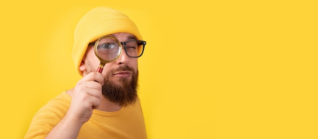 Man with magnifier over yellow background, panoramic layout
